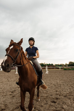 Young girl riding horse in paddock