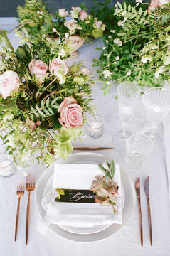 From above an elegant wedding reception tabletop with overgrown greenery, soft copper accents and pink florals