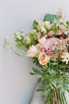 Overgrown wildflower bouquet closeup against a grey linen backdrop