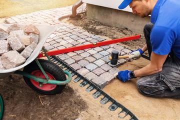 worker laying granite cobblestone pathway around the house