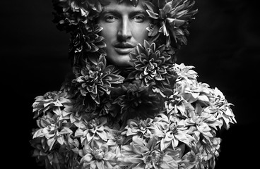 Fashionable portrait of a guy covered with flowers