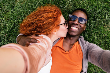 Embracing diverse couple chilling on grass