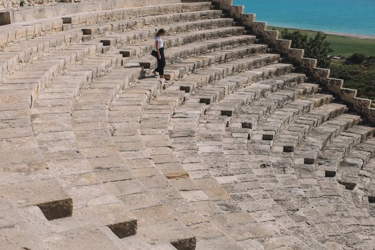 Stylish woman running by  stairs of amphitheater in sunny weather