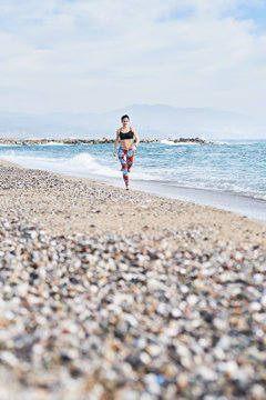 Sportive woman jogging on seashore