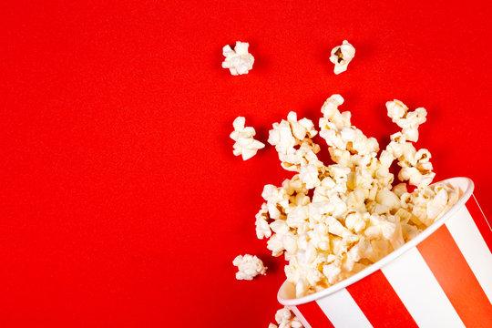 Movie night concept - pop corn, glasses, bright red background