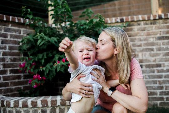 loving mother kisses her toddler during a temper tantrum