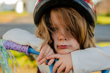 A little girl wearing a bicycle helmet and leaning on a bike handlebar