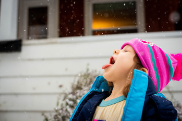 Girl sticks her tongue out to catch snow