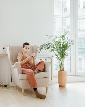 Young woman using smartphone in armchair
