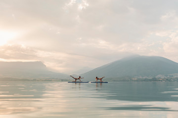 Young woman doing Pilates on a SUP board in the lake at sunrise