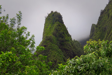 Iao Needle green peak surrounded by misty clouds, Iao Valley State Park, Maui, Hawaii, USA