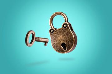 Fototapeta levitating closed bronze lock with key on azure background obraz