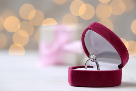 Box with ring on table against blurred lights. Space for text
