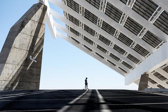 Skateboarder on street with solar panels