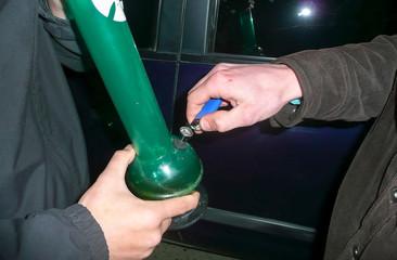 Ignition of cigarette lighter in a bong. Bong smoking. Smoking through the bong is marijuana.