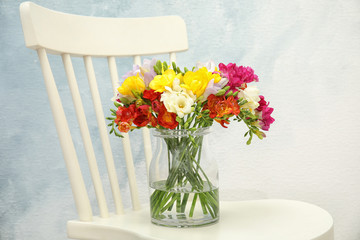 Beautiful bright freesia flowers in vase on chair