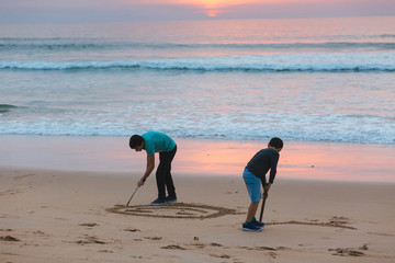 Brothers drawing in sand at sunset