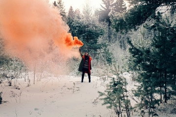 Teenage girl with flare in forest during winter