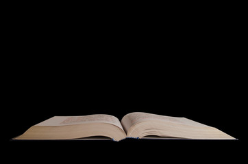 A large open book on a black background. Isolated object.