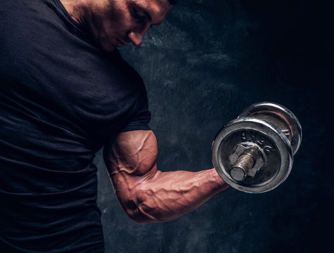 Muscular attractive bodybuilder lifting a barbell