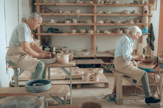 Side view of two potters making earthenware and working in their workshop