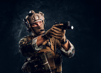 Elite unit, special forces soldier in camouflage uniform holding a gun with a flashlight and laims at the target.