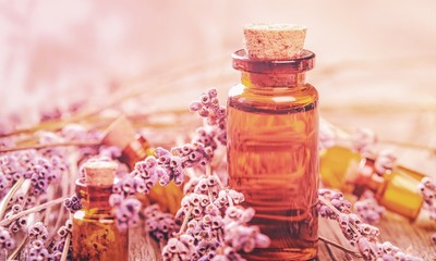 Pile of lavender flowers and a dropper bottle with lavender essence