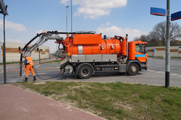 Cleaning sewer manholes. Worker and specialist car.