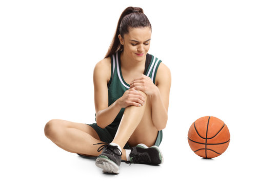Young female basketball player sitting on a floor and holding her painful knee
