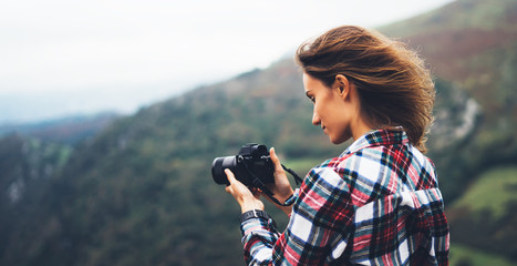 hipster tourist girl hold in hands modern photo camera, photographer look on camera technology take photography click, journey landscape vacation concept, wind mountain
