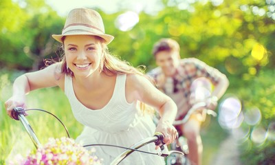 Happy young couple cycling through the park