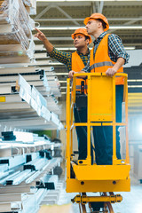 serious indian worker pointing with finger at construction materials while standing on scissor lift near colleague