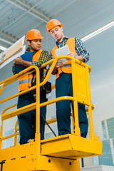concentrated multicultural workers with digital tablet and clipboard standing on scissor lift