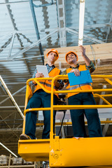 smiling multicultural workers with digital tablet and clipboard standing on scissor lift in warehouse