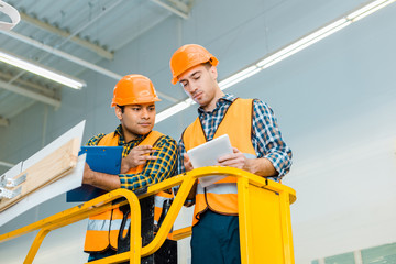 thoughtful multicultural workers with digital tablet and clipboard standing on scissor lift