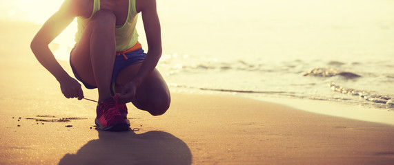 Woman runner tying shoelace ready to run on beach