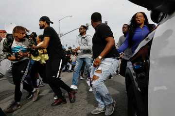 People run away as LAPD officers try to regain control of the crowd following a stampede after fans filled the streets while waiting for the funeral procession for rapper Nipsey Hussle in Los Angeles