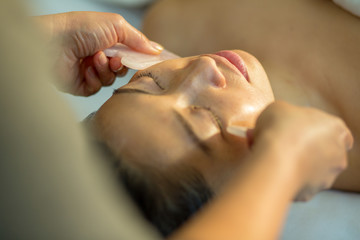 Young woman receives facial rejuvenation with gua sha rose quartz in spa wellness center