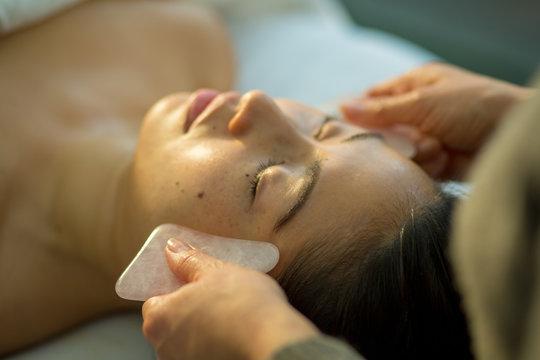 Young woman receives facial rejuvenation with gua sha rose quartz in spa wellness center