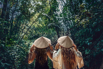 two beautiful young woman in asian hats walking in bamboo forest