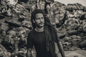 Handsome young man with dreadlocks outdoors. male model at the rocks