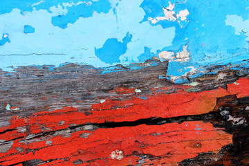 Close up detail of an old boat's hull forms an abstract textured background of old decaying wooden boat panels with colorful bands of bright red and sky blue peeling paint.