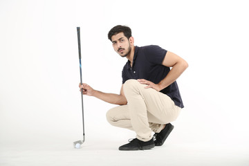 Picture of young boy sitting with golf stick and golf ball. Isolated on white background.