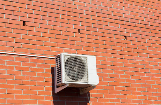 the air conditioning system is installed outside on a brick wall