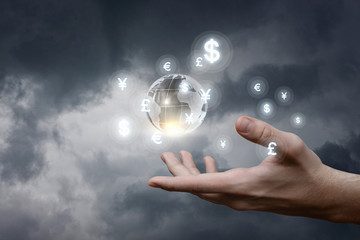 A hand holding a globe surrounded by currency units.