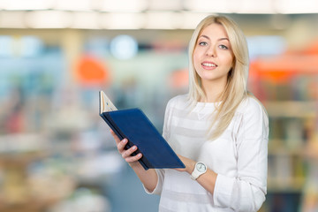 blonde businesswoman writing notes in the clipboard