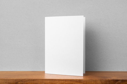 front view of greeting card on bookshelf and grey wall