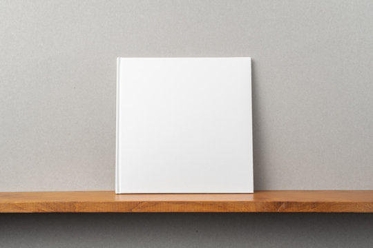 white square notebook on bookshelf and grey wall