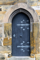 Stone arch and wooden door with decorative elements