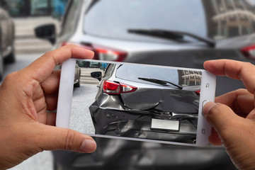 Car insurance agents take pictures of accident-damaged with smartphone for insurance claim.